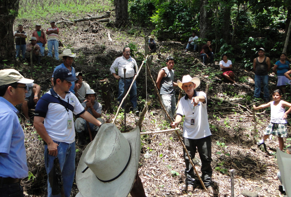 Farmers in Chiquimula and agriculture minister Élmer López observe as a government official shows them how to protect their farmlands against erosion