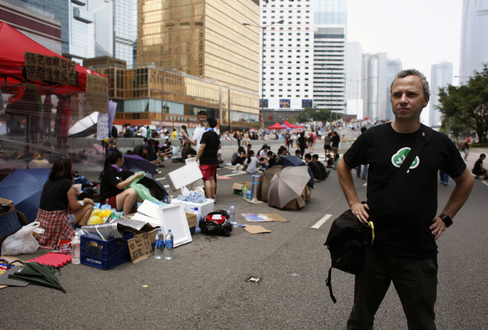 "Micha Benoliel, CEO and co-founder of Open Garden, poses on a main road that pro-democracy protesters have blocked at the Central financial district in Hong Kong October 2, 2014. Open Garden makes FireChat, one of the most popular messaging apps being used by the ""Occupy Central"" civil disobedience movement to communicate and coordinate. The company says over 200,000 new users have downloaded the app in Hong Kong alone in the last two days.  REUTERS/Bobby Yip  (CHINA - Tags: BUSINESS SCIENCE TECHNOLOGY TELECOMS POLITICS CIVIL UNREST) - RTR48LUS"