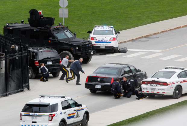 Police officers take cover near Parliament Hilll following a shooting incident in Ottawa October 22, 2014.  A Canadian soldier was shot at the Canadian War Memorial and a shooter was seen running towards the nearby parliament buildings, where more shots were fired, according to media and eyewitness reports.     REUTERS/Chris Wattie (CANADA  - Tags: POLITICS CRIME LAW TPX IMAGES OF THE DAY)   - RTR4B6NX