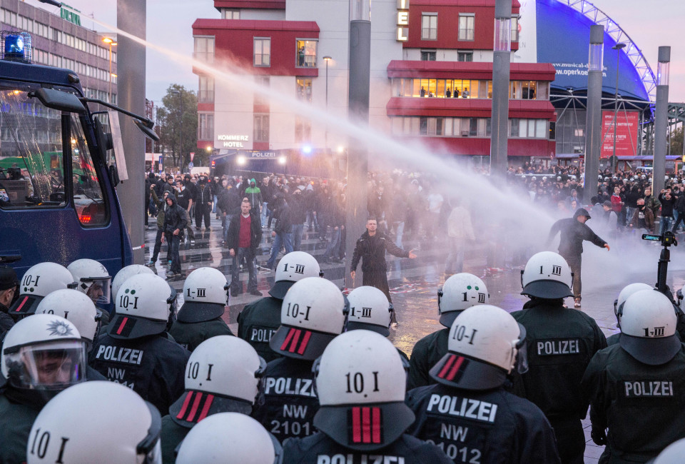 A wall of police pushed a crowd of largely neo-Nazi protesters back from the main train station in Cologne with fire hoses, batons and pepper sprayed.