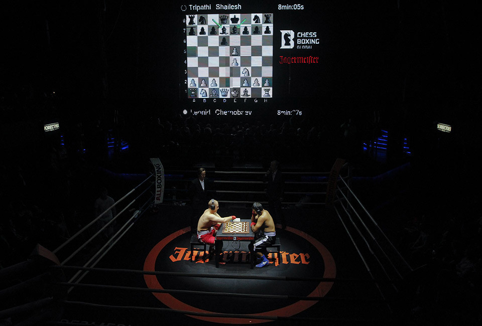 Leonid Chernobayev (L) of Belarus competes against India's Tripathi Shaliesh during their light heavyweight World Championship chessboxing match in Moscow November 28, 2013. Chessboxing alternates between a round of chess and a round of boxing in three minute intervals, and demands the most of its competitors, both mentally and physically. Picture taken November 28, 2013.REUTERS/Maxim Shemetov (RUSSIA - Tags: SPORT SOCIETY TPX IMAGES OF THE DAY CHESS) - RTX15WX9