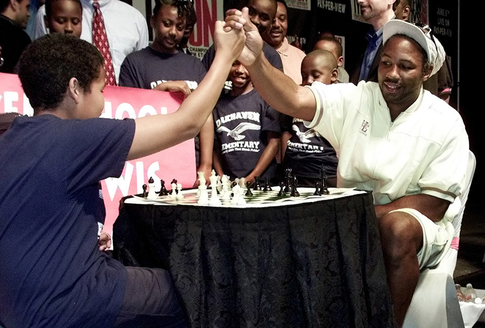 Lennox Lewis (R) high fives with Carlos Harbert after the two played chess during a press conference at a Tunica, Mississippi casino, June 5, 2002. Lewis and Mike Tyson are set to square off for their heavyweight boxing match in Memphis, Tennessee on June 8. REUTERS/Jeff Mitchell  JM/MMR - RTRWATQ