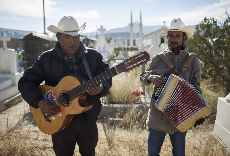 Domingo Pineda (with guitar) and Mario Muñoz (with accordion) perform in the Tepeyac graveyard, in Ciudad Juárez, Mexico, Thursday, November 13, 2014. They belong to a band named 'Si Kantamos Norteño, that perform in the grave yard.