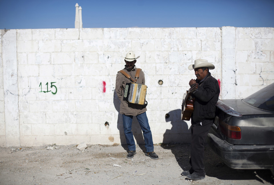 Domingo Pineda (with guitar) and Mario Muñoz (with accordion) wait for customers in the Tepeyac graveyard, in Ciudad Juárez, Mexico, Thursday, November 13, 2014. They belong to a band named 'Si Kantamos Norteño, that perform in the grave yard.