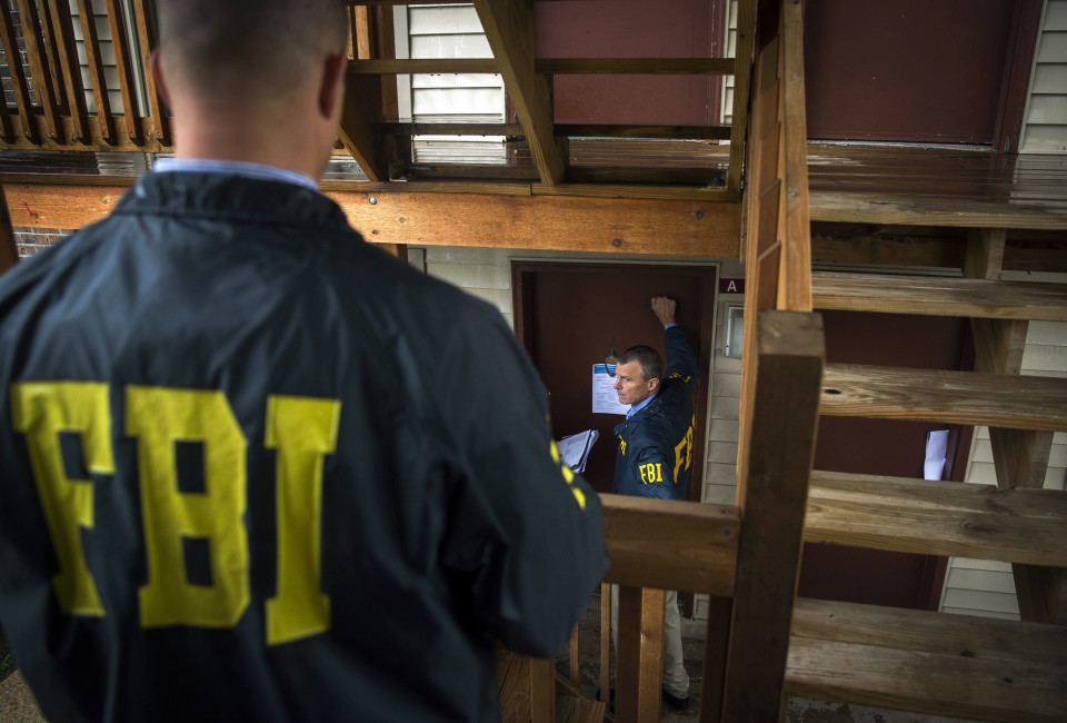 Federal Bureau of Investigation (FBI) agents go door to door to interview residents of the neighborhood for an investigation.