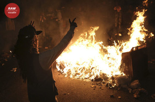 A protester stands near a pile of burning trash during a demonstration in Oakland, California following the grand jury decision in the shooting of Michael Brown in Ferguson, Missouri November 24, 2014. Protests were also staged in New York, Chicago, Washington, D.C. and Seattle over the case that has highlighted long-standing racial tensions not just in predominantly black Ferguson but across the United States. REUTERS/Elijah Nouvelage (UNITED STATES - Tags: CIVIL UNREST) - RTR4FGGG