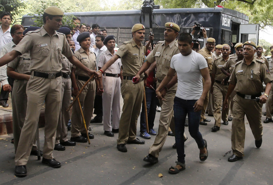 Vinay Sharma (wearing white T-shirt), one of the four men who were sentenced to death for fatally raping a young woman on a bus last December, is escorted by police outside a court in New Delhi September 24, 2013. New Delhi's High Court on Tuesday adjourned a hearing in a case aimed at confirming the death sentence given to four men convicted for raping and murdering a woman in the city last December. REUTERS/Stringer (INDIA - Tags: CRIME LAW) - RTX13XJZ