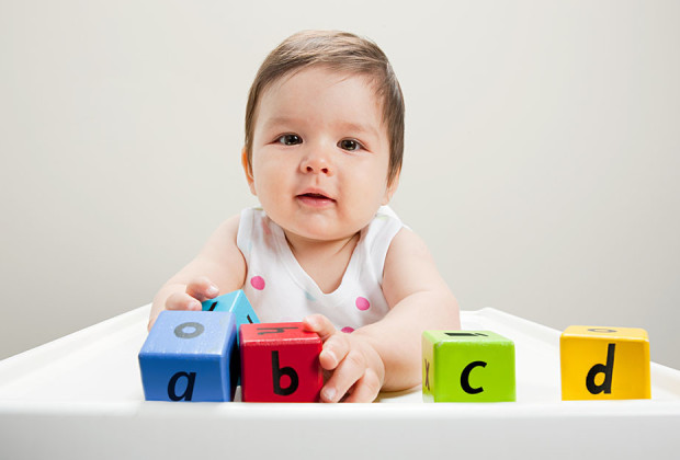 Baby boy sitting in highchair with wooden alphabet blocks --- Image by © Image Source/Corbis