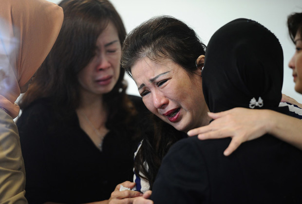 Surabaya Mayor Tri Rismaharini (R) grieves with relatives of missing AirAsia flight QZ8501 passengers at the crisis centre of Juanda International Airport Surabaya on December 29, 2014 in Surabaya, Indonesia. AirAsia announced the flight QZ8501 from Surabaya to Singapore, with 162 people on board, lost contact with air traffic control at 07:24 a.m. local time of December 28.