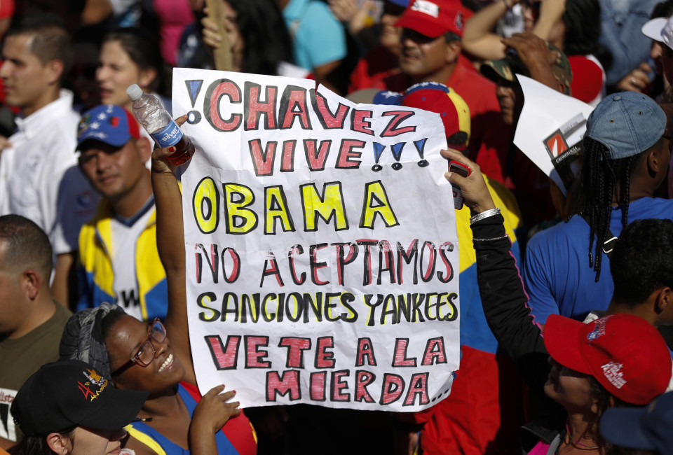"Supporters of Venezuela's President Nicolas Maduro hold a banner during a rally to reject the sanctions that the U.S. government seeks to impose on officials accused of human rights violations, in Caracas December 15, 2014. The banner reads, ""Chavez lives. Obama we don't accept yankees sanctions, go to hell"". REUTERS/Carlos Garcia Rawlins (VENEZUELA - Tags: POLITICS) - RTR4I4QH"