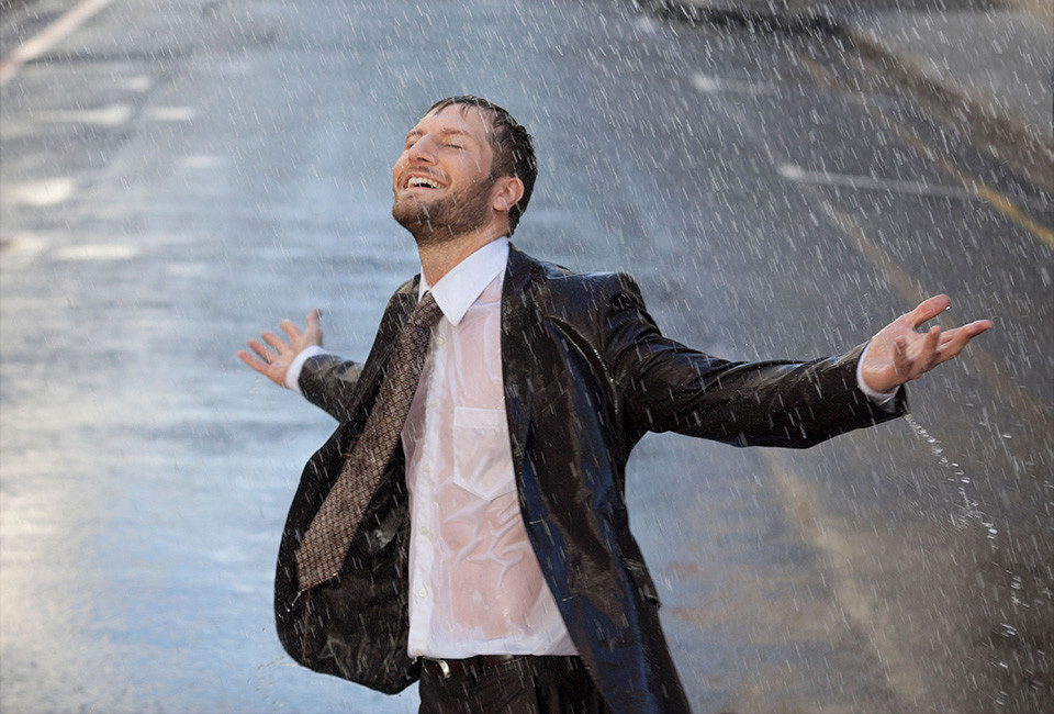DC00R5 Happy businessman with arms outstretched in rainy street. Image shot 2013. Exact date unknown.