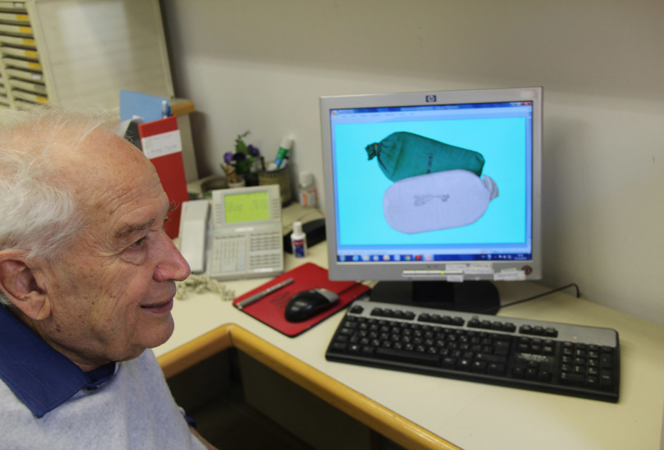 Professor Raphael Mechoulam next to a photo of the Hashish the police supply him, for his research.