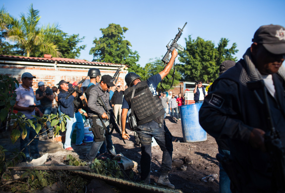 A group of men led by Hipolito Mora fire off their guns at the funeral of Manuel Mora, son of Hipolito, in La Ruana, Michoacán, Mexico, December 18, 2014.