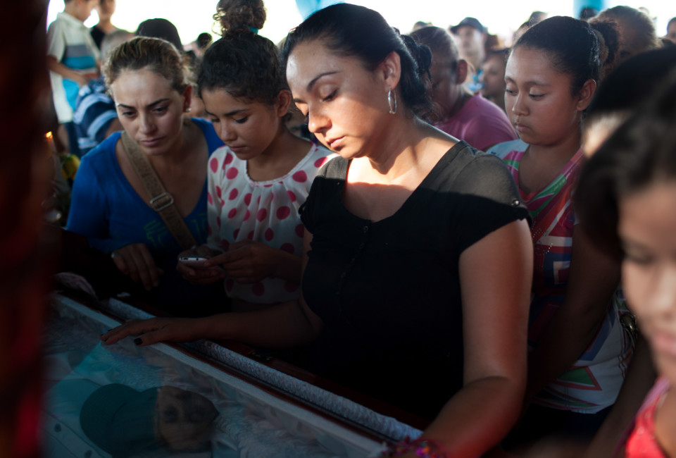 The wife of Manuel Mora (name withheld), centre, looks over his casket, in La Ruana, Michoacán, Mexico, December 18, 2014. Manuel Mora was killed in a confrontation between two rival vignette groups.