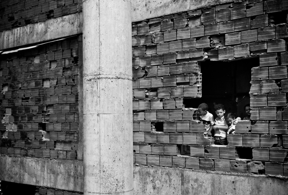 A group of kids watch outside trough a hole in the wall. Despite the efforts of community risk is all around the unfinished infrastructure of the tower with open windows, stairs and balconies.