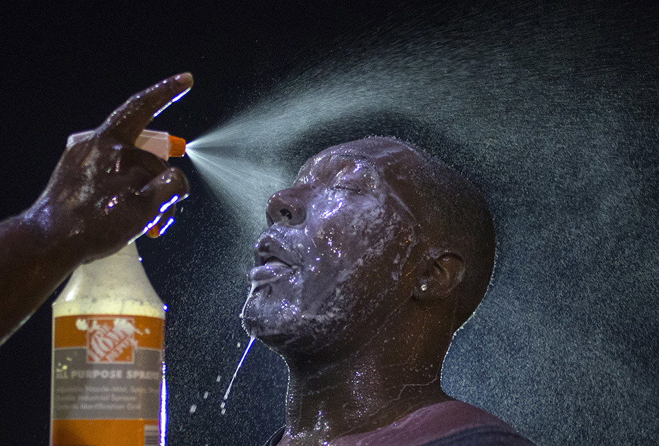 A man is doused with milk and sprayed with mist after being hit by an eye irritant from security forces trying to disperse demonstrators protesting against the shooting of Brown in Ferguson