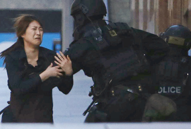 A hostage runs towards a police officer outside Lindt cafe, where other hostages are being held, in Martin Place in central Sydney December 15, 2014. Two more hostages have run out of the cafe at the center of a siege in Sydney, Australia's largest city, according to a Reuters witness at the site. The two women were both wearing aprons indicating they were staff at the Lindt cafe where a gunman has been holding an unknown number of hostages for several hours. Three men had earlier run out of the cafe. REUTERS/Jason Reed (AUSTRALIA - Tags: CRIME LAW CIVIL UNREST TPX IMAGES OF THE DAY) - RTR4I0B0
