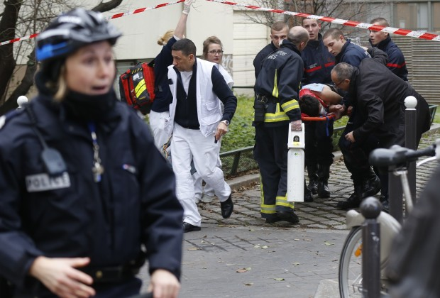 Firefighters carry a victim on a stretcher at the scene after a shooting at the Paris offices of Charlie Hebdo, a satirical newspaper, January 7, 2015. Eleven people including two police officers were killed and 10 injured in shooting at the Paris offices of the satirical weekly Charlie Hebdo, already the target of a firebombing in 2011 after publishing cartoons deriding Prophet Mohammad on its cover, police spokesman said. Five of the injured were in a critical condition, said the spokesman. Separately, the government said it was raising France's national security level to the highest notch.
