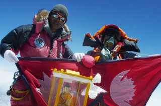 """Nepalese mountaineer Pemba Dorje Sherpa (L) who currently holds the record for the fastest ascent of Everest at eight hour and 10 minutes unfurls a Nepalese flag as he stands with fellow mountaineers at the summit of Everest on May 19, 2009, after ascending from the south face of Nepal.    Bad weather conditions forced three Nepalese Sherpa brothers to give up their plans to set a new world record by spending 24 hours in the """"death zone"""" on top of Mount Everest. Pemba Dorje Sherpa, 30, and his two younger brothers reached the summit on May 19, but were forced down after only two hours, Pemba told AFP after returning to Kathmandu.      AFP PHOTO/COURTESY OF PEMBA DORJE SHERPA (Photo credit should read STR/AFP/Getty Images)"""