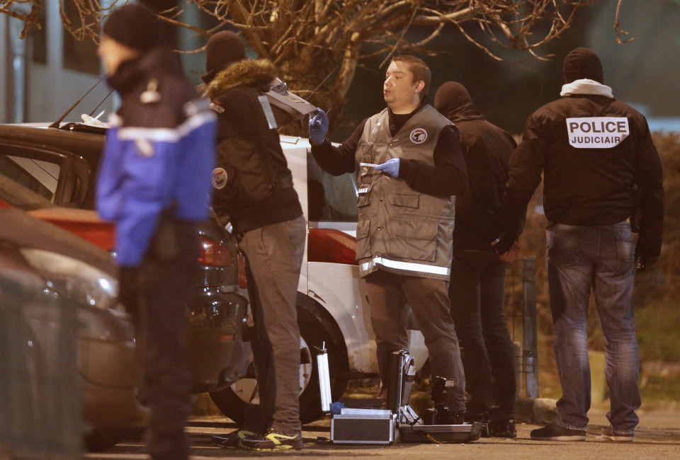 Police investigators search for evidence as an unidentified man is detained (2nd R) during an operation in the eastern French city of Reims January 8, 2015, after the shooting against the Paris offices of Charlie Hebdo, a satirical newspaper. No further information about the man has been released. An 18-year old man sought by police over Wednesday's shooting attack at the magazine handed himself voluntarily to police in northeastern France, an official at the Paris prosecutor's office said. Police are hunting three French nationals, including brothers Said Kouachi, born in 1980; Cherif Kouachi, born in 1982; and Hamyd Mourad born in 1996, after suspected Islamist gunmen killed 12 people. REUTERS/Christian Hartmann (FRANCE  - Tags: CRIME LAW MEDIA) - RTR4KHIQ