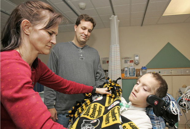 """Beth Malarkey, left, covers up her son, Alex, right, with a blanket after surgery as Alex's father, Kevin, watches at University Hospital's Case Western Reserve Medical Center in Cleveland. Alex Malarkey was in a 2004 car crash left him paralyzed below the neck and was receiving an artificial breathing device. Spokesman Todd Starowitz of Tyndale House, a leading Christian publisher, confirmed Friday, Jan. 16, 2015, that Alex Malarkey's """"The Boy Who Came Back from Heaven: A Remarkable Account of Miracles, Angels, and Life Beyond This World"""" was being withdrawn. Earlier this week, Alex Malarkey acknowledged in an open letter that he was lying, saying that he had been seeking attention."""