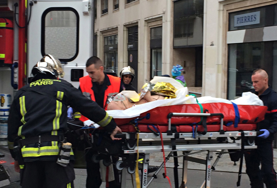 "Firefighters carry an injured man on a stretcher in front of the offices of the French satirical newspaper Charlie Hebdo in Paris on January 7, 2015, after armed gunmen stormed the offices leaving at least one dead according to a police source and ""six seriously injured"" police officers according to City Hall. AFP PHOTO / PHILIPPE DUPEYRAT        (Photo credit should read Philippe Dupeyrat/AFP/Getty Images)"