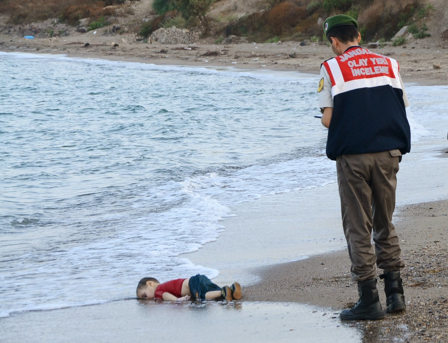 ATTENTION EDITORS - VISUAL COVERAGE OF SCENES OF DEATH OR INJURY A Turkish gendarmerie stands next to a young migrant, who drowned in a failed attempt to sail to the Greek island of Kos, as he lies on the shore in the coastal town of Bodrum, Turkey, September 2, 2015. At least 11 migrants believed to be Syrians drowned as two boats sank after leaving southwest Turkey for the Greek island of Kos, Turkey's Dogan news agency reported on Wednesday. It said a boat carrying 16 Syrian migrants had sunk after leaving the Akyarlar area of the Bodrum peninsula, and seven people had died. Four people were rescued and the coastguard was continuing its search for five people still missing. Separately, a boat carrying six Syrians sank after leaving Akyarlar on the same route. Three children and one woman drowned and two people survived after reaching the shore in life jackets.  REUTERS/Nilufer Demir/DHA  TPX IMAGES OF THE DAY  ATTENTION EDITORS - NO SALES. NO ARCHIVES. FOR EDITORIAL USE ONLY. NOT FOR SALE FOR MARKETING OR ADVERTISING CAMPAIGNS. TEMPLATE OUT. THIS IMAGE HAS BEEN SUPPLIED BY A THIRD PARTY. THIS PICTURE WAS PROCESSED BY REUTERS TO ENHANCE QUALITY. AN UNPROCESSED VERSION WILL BE PROVIDED SEPARATELY. TURKEY OUT. NO COMMERCIAL OR EDITORIAL SALES IN TURKEY.