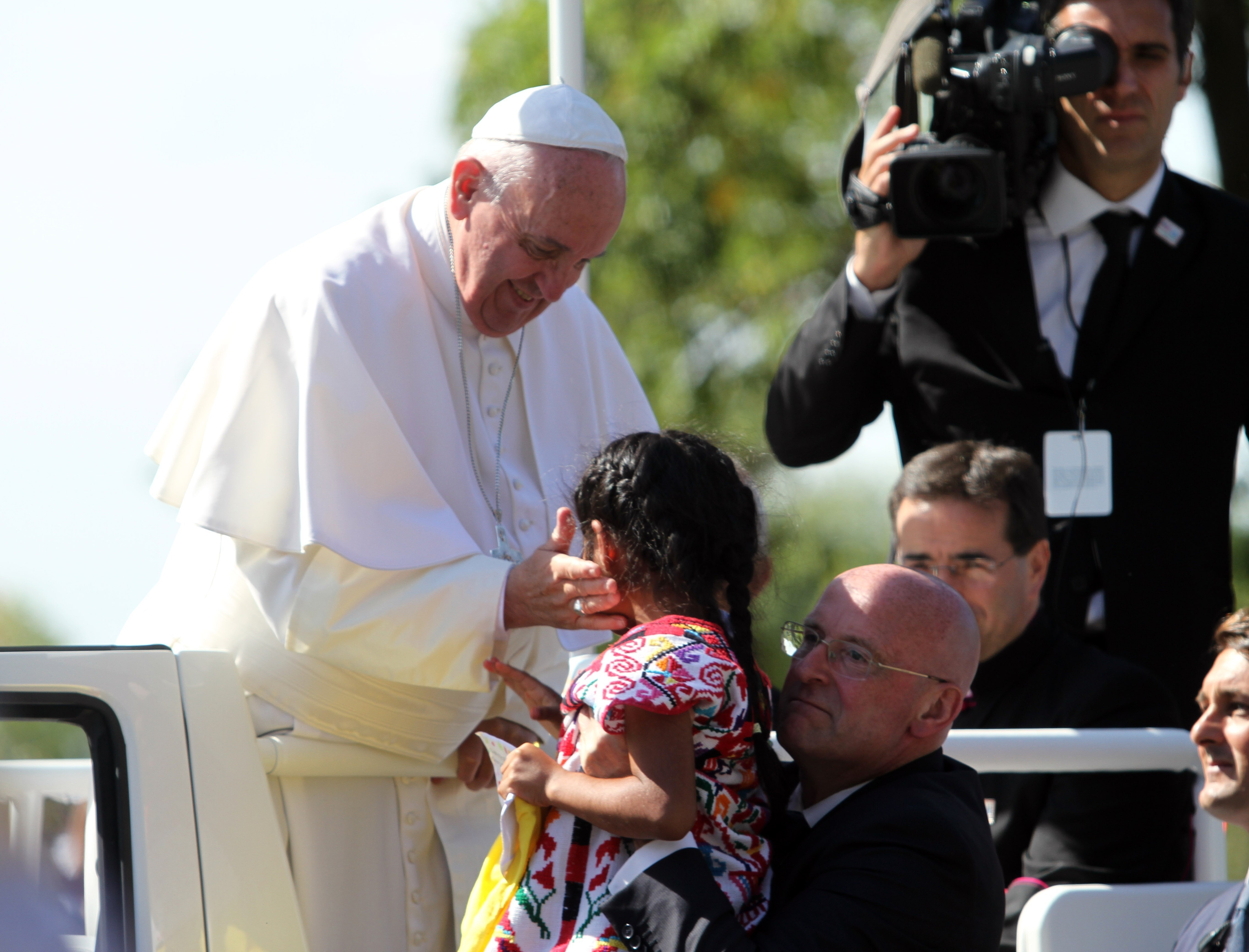 WASHINGTON D.C, UNITED STATES - SEPTEMBER 23: Pope Francis takes care with a little girl, named Sopihe, after she broke security measures and ran towards him during a parade in Washington D.C, United States on September 23, 2015. (Photo by Esra Kaymak/Anadolu Agency/Getty Images)