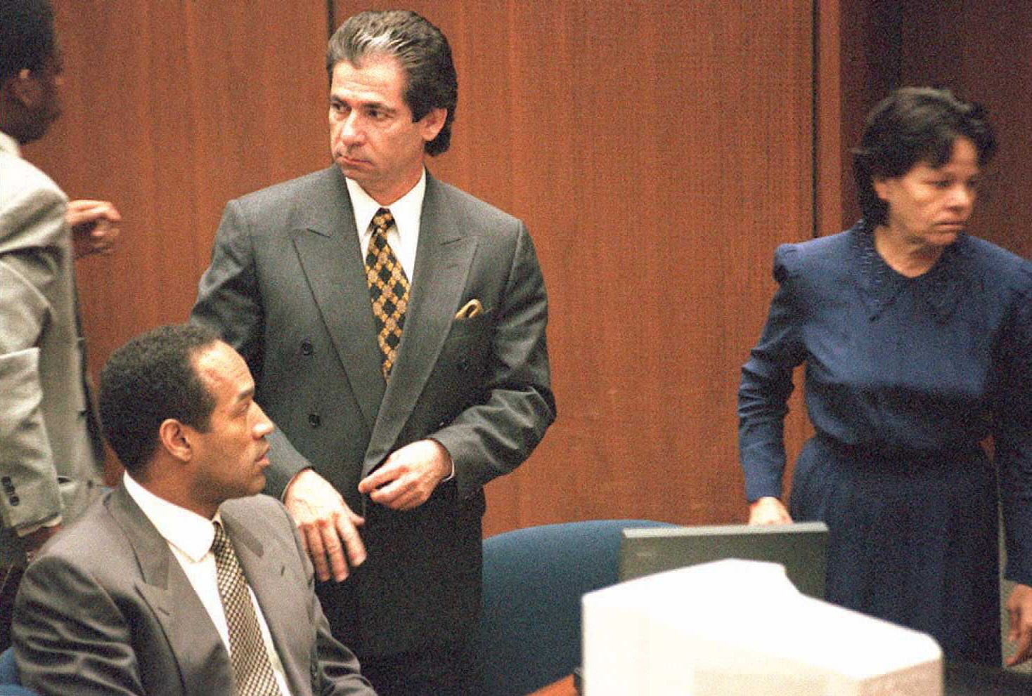LOS ANGELES, CA - FEBRUARY 27:  Murder defendant O.J. Simpson(L, sitting) watches defense witness Rosa Lopez enter the court for a hearing on how her testimony will be heard 27 February. Superior Court Judge Lance Ito decided that Lopez's testimony will be videotaped without a jury present. Standing next to Simpson is Robert Kardashian. (COLOR KEY:Lopez has blue dress.)   AFP PHOTO  (Photo credit should read POO/AFP/Getty Images)
