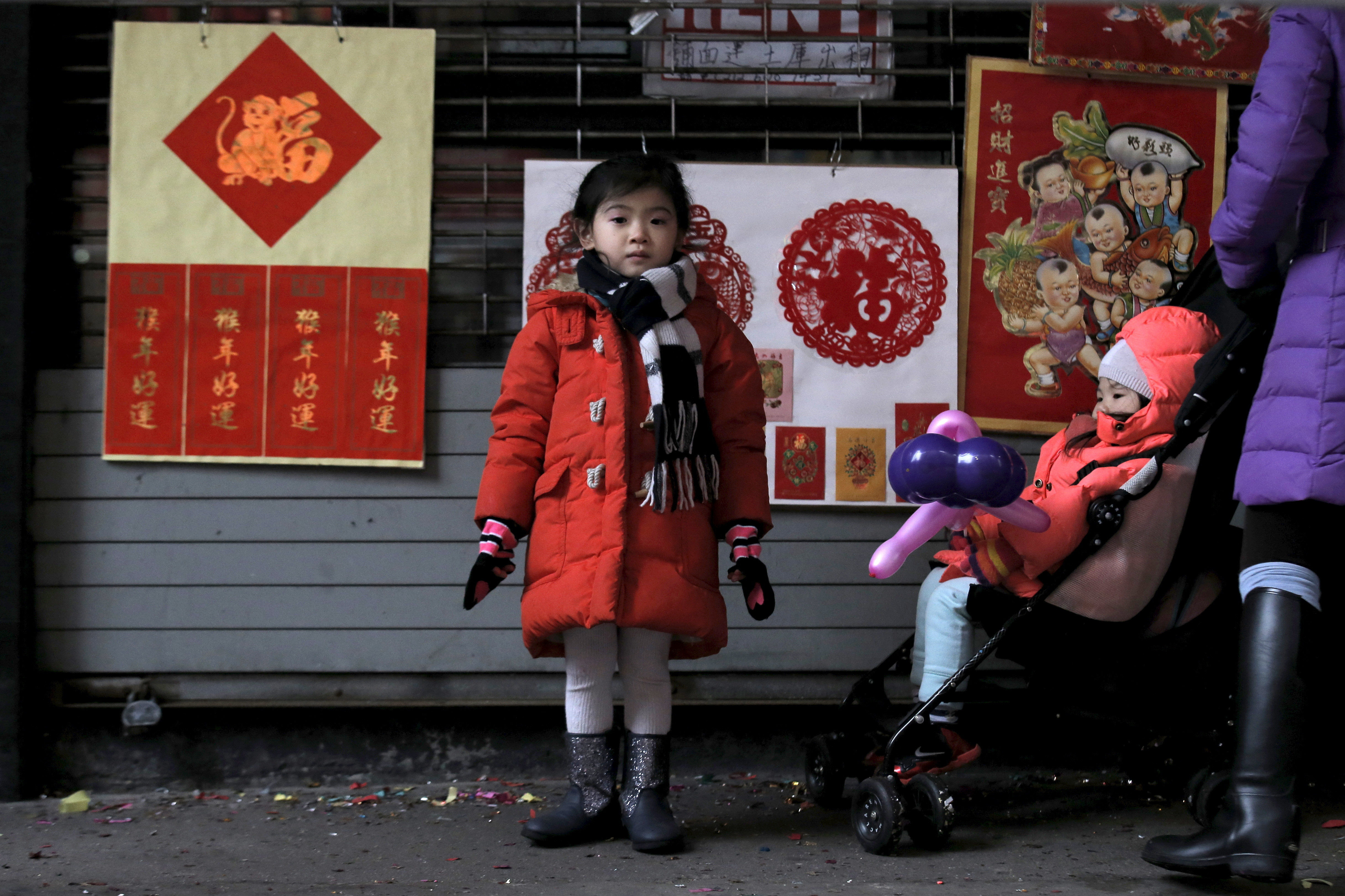 A little girl watches a lion dance during the celebration of the Chinese Lunar New Year in Manhattan's Chinatown in New York February 8, 2016. REUTERS/Brendan McDermid  - RTX262EB
