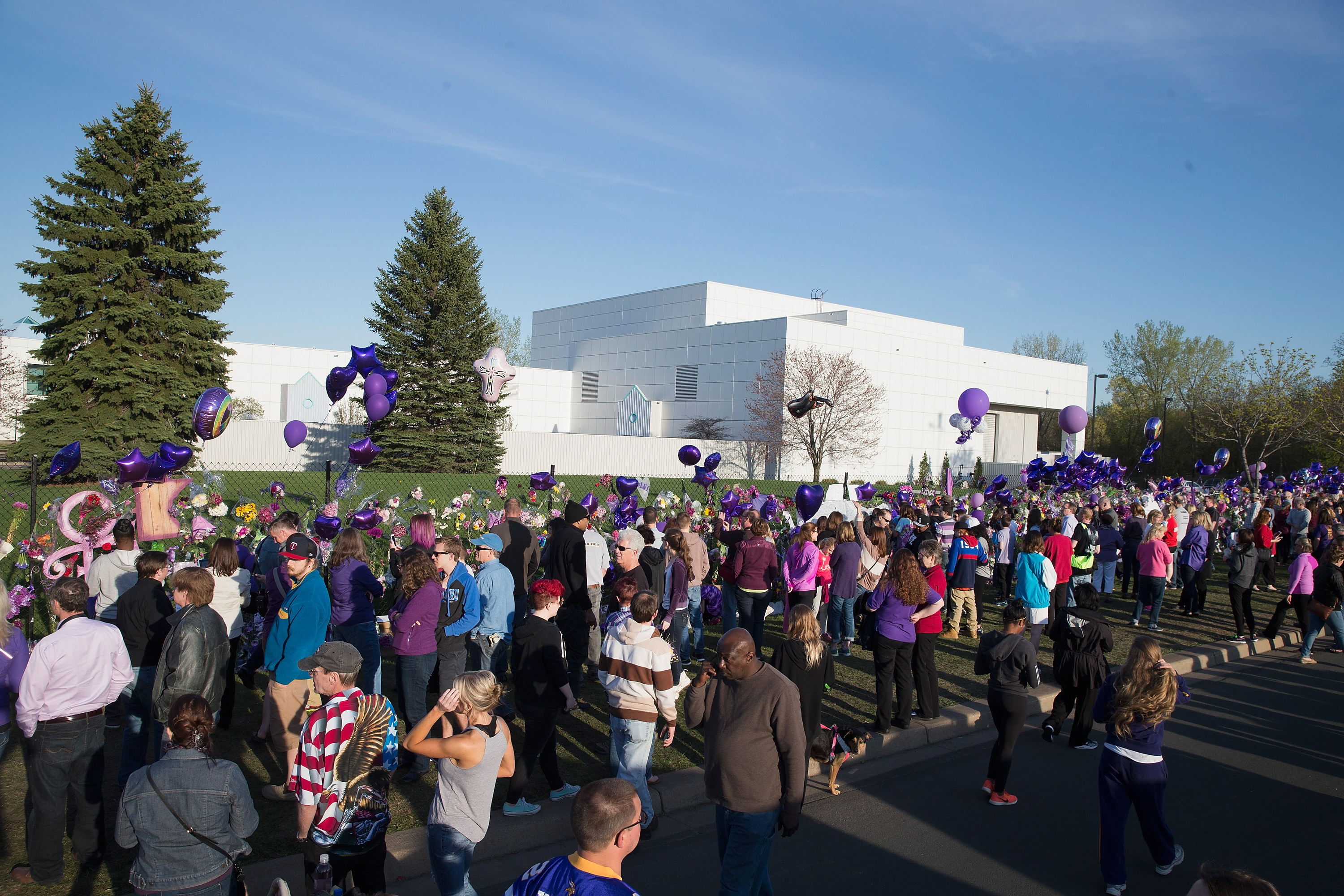 CHANHASSEN, MN - APRIL 22:  Music fans visit a memorial outside Paisley Park, the home and studio of Prince, on April 22, 2016 in Chanhassen, Minnesota. Prince, 57, was pronounced dead shortly after being found unresponsive yesterday at Paisley Park.  (Photo by Scott Olson/Getty Images)