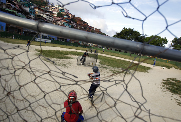 """Children practice during a baseball game at the """"Mamera"""" neighborhood in Caracas March 10, 2011. Boys as young as five years old are training in Venezuela's Little Leagues. Some of them live in the city's slums or poorer neighborhoods and think baseball could be a ticket to a different life. Being a major league baseball player is the dream of thousands of children, but in Venezuela it is also a chance for a brighter future. In 2010 a record 58 Venezuelans played in Major League Baseball in the United States, making up more than a quarter of all the players born outside the U.S. Between 1939 and 2010 a total of 258 Venezuelans have gone on to play in major league teams in the United States. Picture taken March 10, 2011. REUTERS/Jorge Silva (VENEZUELA - Tags: SPORT BASEBALL SOCIETY) - RTR2JY1N"""