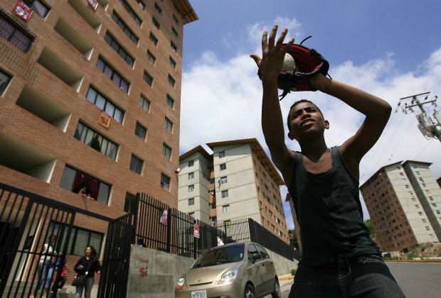 A child plays baseball outside a new apartment block in the neighborhood of San Agustin in Caracas February 9, 2009. Cheap housing, health clinics and even a new cable car have kept President Hugo Chavez popular in the Caracas slum of San Agustin throughout a turbulent decade and help explain why Venezuelans may approve the socialist leader's bid to extend his rule. Picture taken February 9, 2009. REUTERS/Alejandro Rustom (VENEZUELA) - RTXBGU3