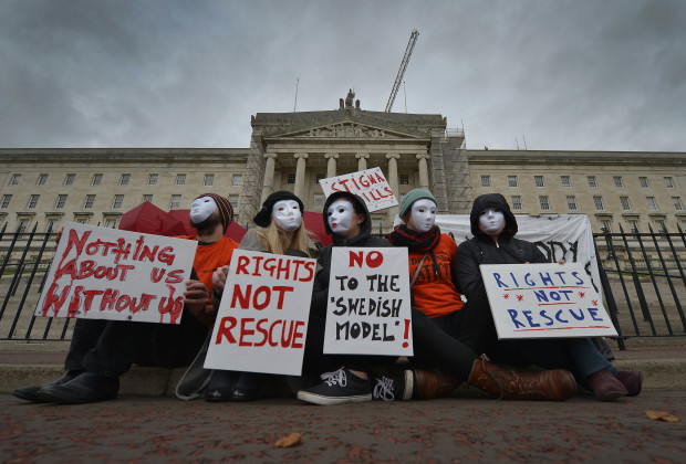 BELFAST, NORTHERN IRELAND - OCTOBER 20: Sex workers wearing masks to protect their identity protest against a proposed human trafficking bill at Stormont on October 20, 2014 in Belfast, Northern Ireland. On Monday night the Northern Ireland Assembly will vote on the Human Trafficking and Exploitation Bill. The bill, drawn up by the DUP peer Lord Morrow, contains a clause that would make it a crime for anyone to pay for sex. Sex workers worry that criminalisation of clients will lead to a potential decrease in security, worsen working conditions and increase risks of violence and other abuse. Research published last week suggested that about 17,500 men pay for sex each year in Northern Ireland. The study by Queen's University, Belfast, was commissioned by the Department of Justice in response to Lord Morrow's proposed bill. Meanwhile, another poll has indicated that almost 80% of people in Northern Ireland support the criminalisation of paying for sex. (Photo by Charles McQuillan/Getty Images)