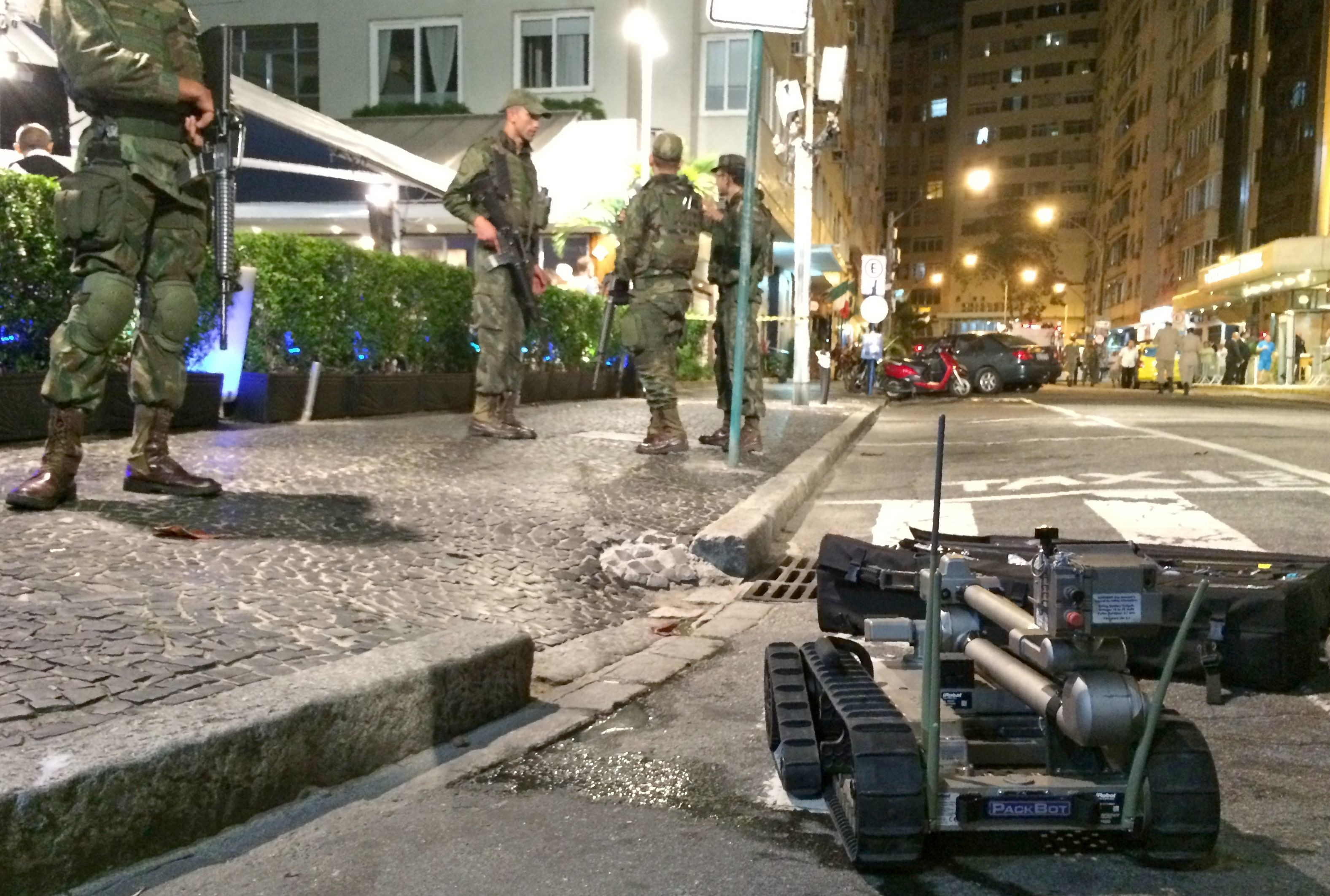 An image taken on a mobile phone shows members of Brazil's armed forces stand on duty as bomb disposal equipment is packed away following a controlled explosion in the Copacabana district of Rio de Janeiro on August 9, 2016. A suspect package was blown up on Tuesday near the luxury beachfront Copacabana Palace hotel. Earlier in the day a bus carrying Rio Olympics journalists came under attack and police were investigating whether bullets were fired from the notorious City of God favela. / AFP / Leon NEAL        (Photo credit should read LEON NEAL/AFP/Getty Images)