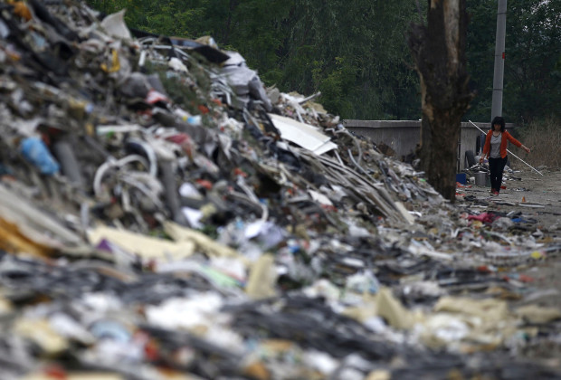 A woman walks near mounds of garbage, which were abandoned by recycling workers, at Dongxiaokou village in Beijing May 18, 2014. On the outskirts of Beijing lies Dongxiaokou village, a major centre for recycling old electronic goods, or e-waste. Discarded electrical and electronic products, from abandoned air-conditioners to refrigerators, are collected and recycled mostly by migrant workers who either repair them or sell them on as scrap. Those in the business in Dongxiaokou grapple with poor infrastructure and sanitation facilities, in addition to dangers associated with handling e-waste. The village is now facing demolition to make way for an ambitious urbanisation plan, and residents are worried about losing their homes and work. Environmental issues will be under the spotlight on June 5, which marks World Environment Day. Picture taken May 18, 2014.   REUTERS/Kim Kyung-Hoon (CHINA - Tags: ENVIRONMENT SOCIETY BUSINESS EMPLOYMENT)  ATTENTION EDITORS: PICTURE 01 OF 25 FOR PACKAGE 'ENVIRONMENT DAY - CHINA'S E-WASTE VILLAGE'  TO FIND ALL IMAGES SEARCH 'DONGXIAOKOU' - RTR3S4LY