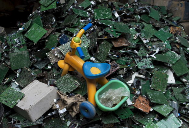 "A toy tricycle is seen on circuit boards at a workshop in the township of Guiyu in China's southern Guangdong province June 8, 2015. The town of Guiyu in the economic powerhouse of Guangdong province in China has long been known as one of the world's largest electronic waste dump sites. At its peak, some 5,000 workshops in the village recycle 15,000 tonnes of waste daily including hard drives, mobile phones, computer screens and computers shipped in from across the world. Many of the workers, however, work in poorly ventilated workshops with little protective gear, prying open discarded electronics with their bare hands. Plastic circuit boards are also melted down to salvage bits of valuable metals such as gold, copper and aluminum. As a result, large amounts of pollutants, heavy metals and chemicals are released into the rivers nearby, severely contaminating local water supplies, devastating farm harvests and damaging the health of residents. The stench of burnt plastic envelops the small town of Guiyu, while some rivers are black with industrial effluent. According to research conducted by Southern China's Shantou University, Guiyu's air and water is heavily contaminated by toxic metal particles. As a result, children living there have abnormally high levels of lead in their blood, the study found. While most of the e-waste was once imported into China and processed in Guiyu, much more of the discarded e-waste now comes from within China as the country grows in affluence. China now produces 6.1 million metric tonnes of e-waste a year, according to the Ministry of Industry and Information Technology, second only to the U.S with 7.2 million tonnes. REUTERS/Tyrone Siu TPX IMAGES OF THE DAY  PICTURE 9 OF 18 FOR WIDER IMAGE STORY ""WORLD'S LARGEST ELECTRONIC WASTE DUMP"" SEARCH ""GUIYU SIU"" FOR ALL IMAGES        TPX IMAGES OF THE DAY      - RTX1IUQ7"