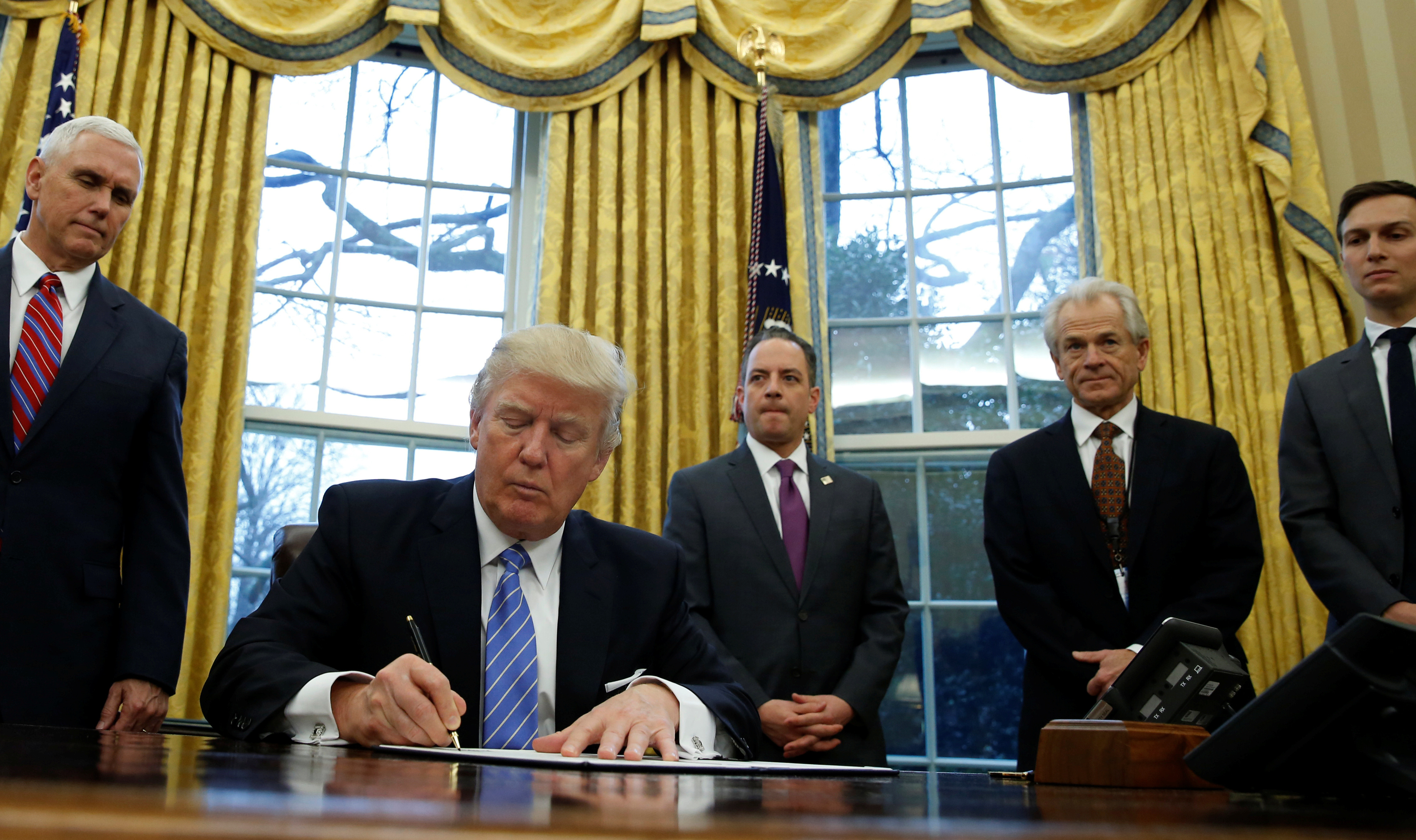 U.S. President Donald Trump, watched by (L-R) Vice President Mike Pence, White House Chief of Staff Reince Priebus, head of the White House Trade Council Peter Navarro and senior advisor Jared Kushner, signs an executive order that places a hiring freeze on non-military federal workers in the Oval Office of the White House in Washington January 23, 2017.   REUTERS/Kevin Lamarque - RTSX01K