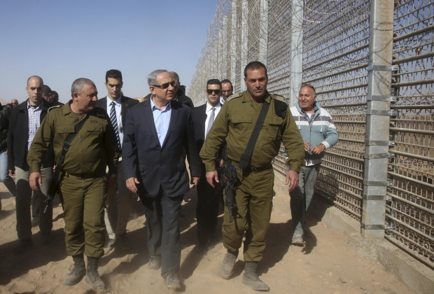 Israeli Prime Minister Benjamin Netanyahu walks next to Chief of Staff Lieutenant General Gadi Eizenkot during a visit to the border fence between Israel and Jordan in southern Israel near Eilat February 9, 2016. REUTERS/Marc Israel Sellem/Pool - RTX267HD