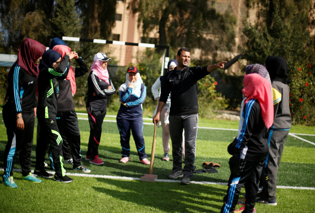 Palestinian baseball coach Mahmoud Tafesh gestures as he trains women in Khan Younis in the southern Gaza Strip March 19, 2017. Picture taken March 19, 2017. REUTERS/Mohammed Salem - RTX31SZW