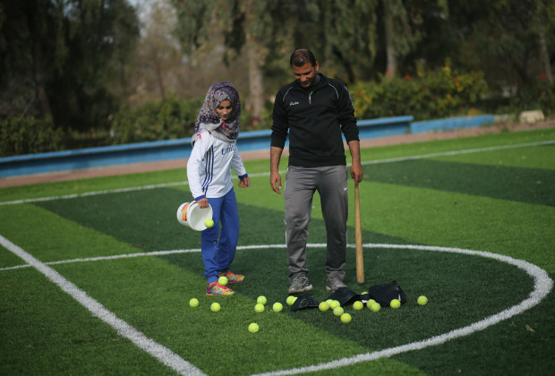 Palestinian baseball coach Mahmoud Tafesh uses a makeshift bat and tennis balls during baseball training session for women in Khan Younis in the southern Gaza Strip March 19, 2017. Picture taken March 19, 2017. REUTERS/Mohammed Salem - RTX31T03