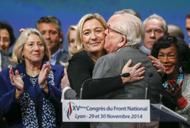 Marine Le Pen (C), France's National Front political party leader, reacts with her father Jean-Marie Le Pen (R) after being re-elected during their congress in Lyon November 30, 2014. REUTERS/Robert Pratta (FRANCE - Tags: POLITICS TPX IMAGES OF THE DAY) - RTR4G3WN