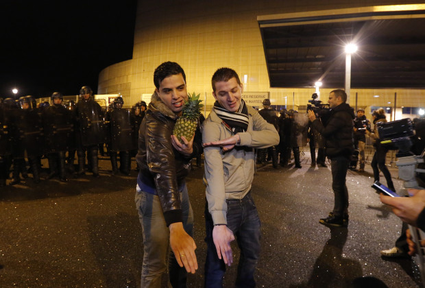 """Youths make a gesture, the """"quenelle"""" outside the Zenith concert hall where French humorist Dieudonne M'bala M'bala, also known as Dieudonne, was to hold his show in Nantes, January 9, 2014. Critics say the comic's trademark straight-arm gesture is a Nazi salute in reverse. Dieudonne, 46, says it is anti-Zionist and anti-establishment, but not anti-Semitic. The Council of State, France's highest administrative court has now reinstated the ban on the show, over-ruling a decision earlier in the day to permit the show by the comedian.    REUTERS/Stephane Mahe (FRANCE - Tags: POLITICS CRIME LAW) - RTX177TB"""