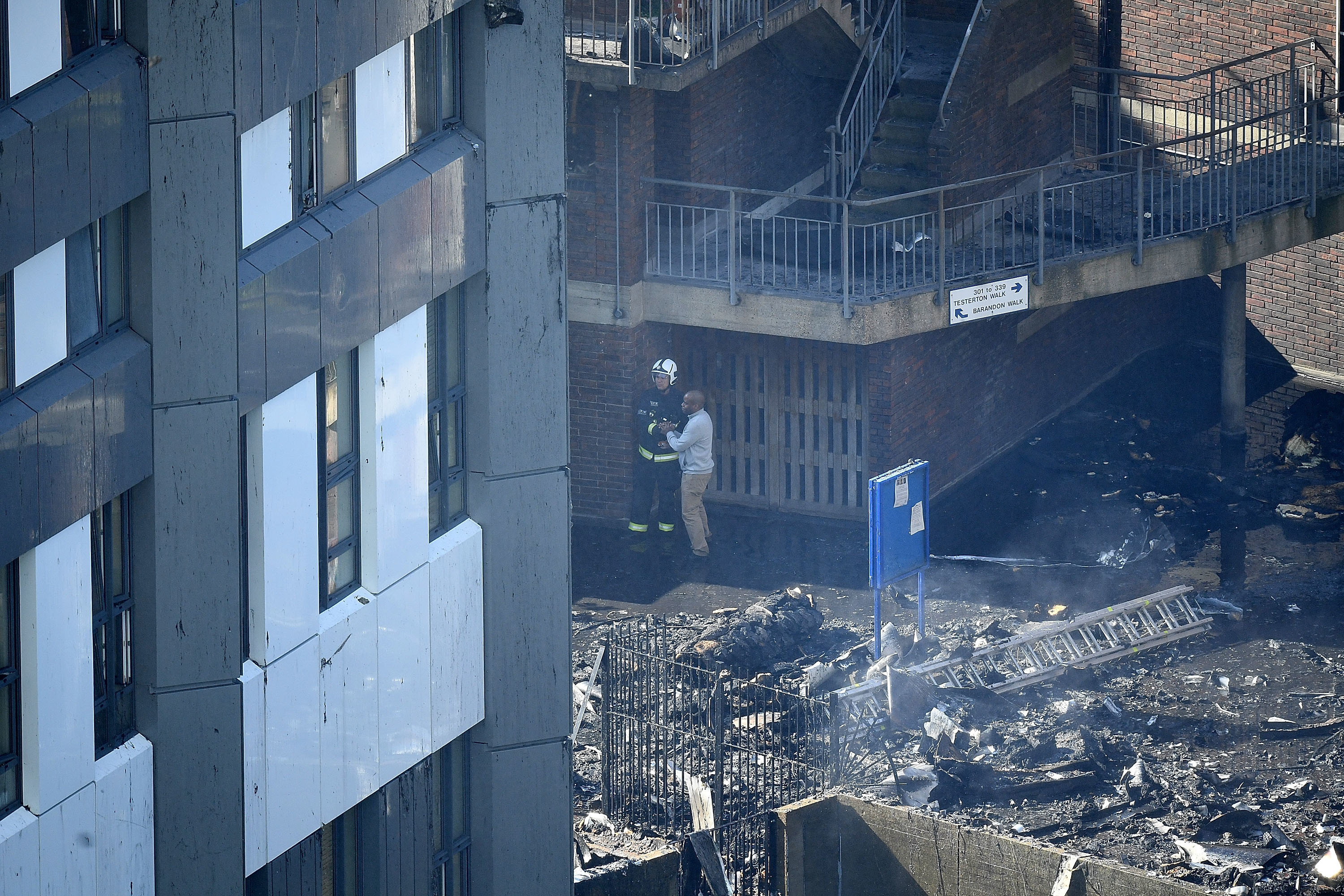 LONDON, ENGLAND - JUNE 14: A man speaks to a fire fighter after a huge fire engulfed the 24 story Grenfell Tower in Latimer Road, West London in the early hours of this morning on June 14, 2017 in London, England.  The Mayor of London, Sadiq Khan, has declared the fire a major incident as more than 200 firefighters are still tackling the blaze, while at least 50 people are receiving hospital treatment.  (Photo by Leon Neal/Getty Images)