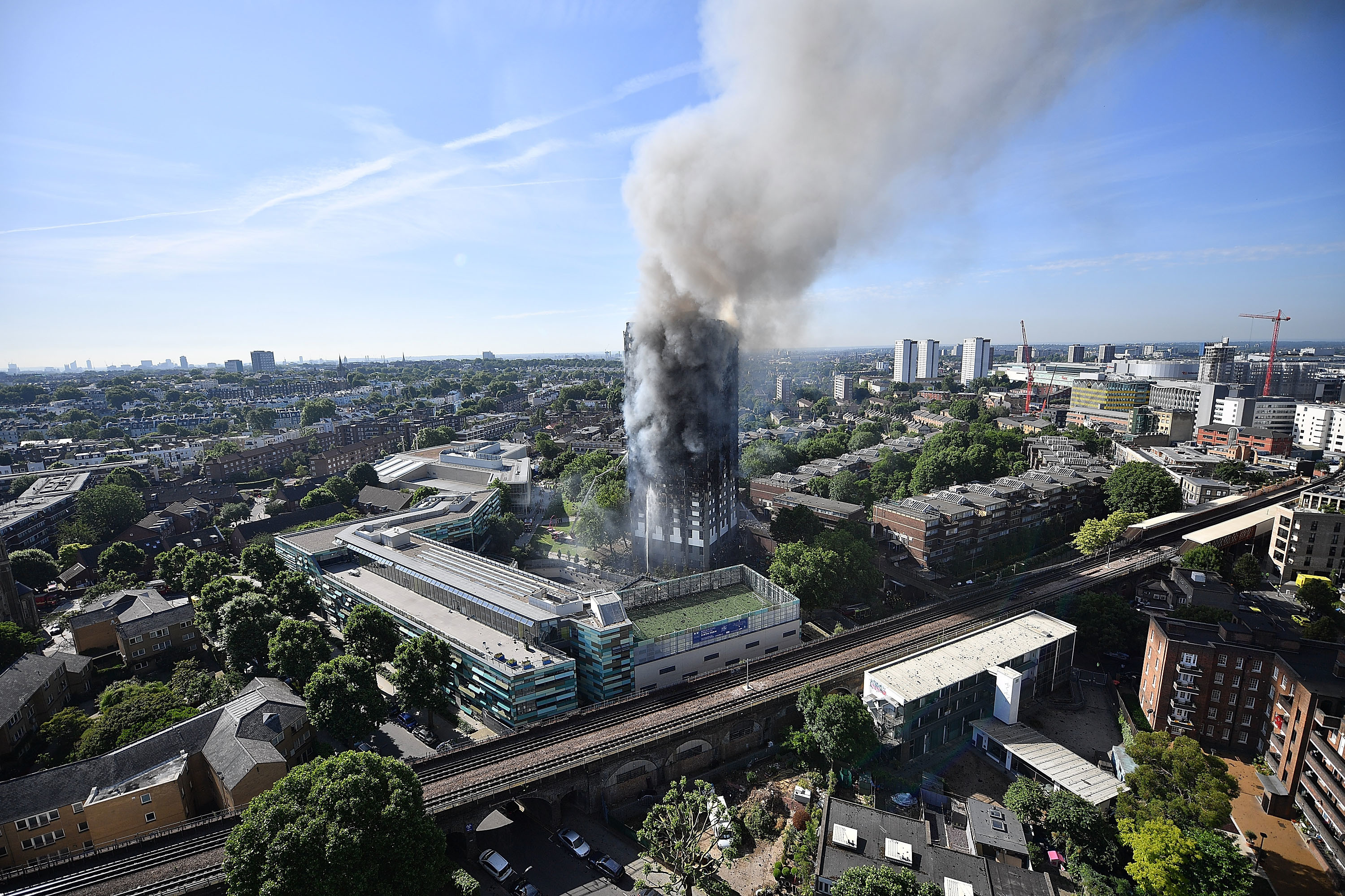 LONDON, ENGLAND - JUNE 14:  Smoke rises from the building after a huge fire engulfed the 24 story Grenfell Tower in Latimer Road, West London in the early hours of this morning on June 14, 2017 in London, England.  The Mayor of London, Sadiq Khan, has declared the fire a major incident as more than 200 firefighters are still tackling the blaze while at least 50 people are receiving hospital treatment.  (Photo by Leon Neal/Getty Images)