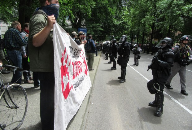 Anti-fascist protesters stand in front of a line of riot police during a free speech rally in Portland on Sunday.